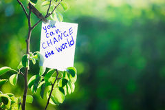 Motivating phrase You can change the world. On a green background on a branch is a white paper with a motivating phrase. Motivating phrase You can change the Royalty Free Stock Photo