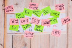 Motivating phrases like Now, can do it, Yes, on sticky notes. Motivating phrases like Now, can do it, Yes, on colour sticky notes above demotivating text like I Royalty Free Stock Images