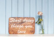 Motivating poster and white rose. Old wooden motivational poster with quote Start doing things you love and rose in the bottle on the bookshelf on blue wooden Stock Images