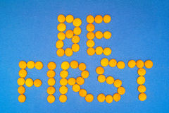 Motivation: Be first. Be First, motivation quote. Letteras are mde of little yellow round on blue background stock images