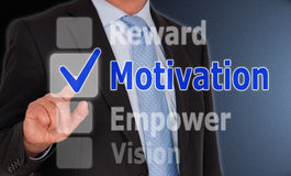 Motivation concept. Businessman in suit and tie checking option motivation on touchscreen with reward, empower and vision as other check box options Stock Photos