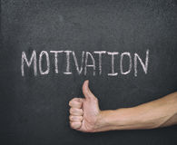 Motivation concept. Thumb up below and word Motivation on blackboard Royalty Free Stock Image
