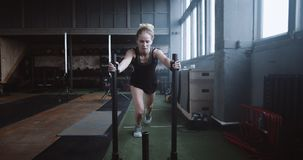 Motivation concept, young athletic blonde woman pushing heavy training sled towards camera training in gym slow motion. Amateur Caucasian female athlete stock video