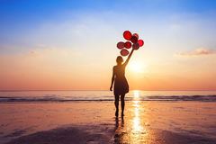 Motivation or hope concept, follow your dream. And inspiration, girl with balloons at sunset royalty free stock images