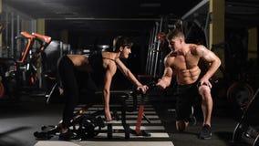 Motivation Liggande armhävning för styrka för idrottshallkvinnaliggande armhävning med hanteln i en konditiongenomkörare uppmuntr stock video