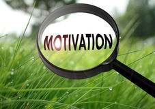 Motivation. Magnifying glass with the word motivation on grass background. Selective focus Royalty Free Stock Photo