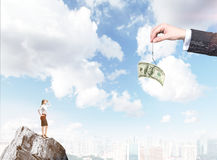 Motivation by money. A hand holding a one-hundred dollar banknote on a thread, a young businesswoman on the rock looking at it. City and blue sky at the Stock Image
