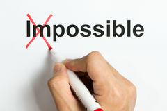 Motivation or positive attitude concept. Hand holding marker pen to cross out the word impossible to reveal possible Royalty Free Stock Photo
