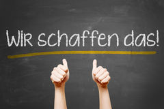 Motivation slogan. We can do it in german language behind business hands with thumbs up Stock Photography