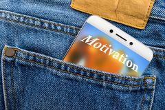 Motivation text concept on the display of a smartphone placed in a jeans pocket. Stock Photo