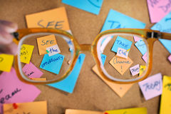 Motivational career messages written on post-its. Messages on post-its over a cork message board. Clear sight through high diopter retro glasses Stock Images