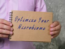 Motivational concept about Optimize Your Microbiome with sign on the piece of paper