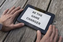 Motivational and inspirational message Be the game changer. Close-up of the hands of a man holding a PC tablet with a motivational and inspirational message Be Royalty Free Stock Images