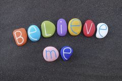 Believe me, motivational words composed with colored stones over black sand. Motivational phrase, Believe me, with colored letters over black volcanic sand stock photography