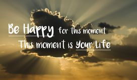 Motivational quote `Be happy for this moment. This moment is your life.` on a background with cloud and rays of sunlight from behi stock photography