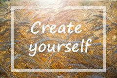 Motivational quote Create yourself in a frame on yellow and orange background of wheat field. Motivational quote `Create yourself` in a narrow white frame on royalty free stock photos