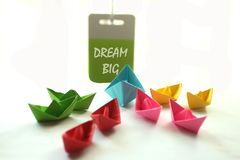 Dream Big. Monday spirit with paper boats and text messages. Motivational quote- Dream Big. With colorful paper boats and a motivation note hanging on the wall royalty free stock photo