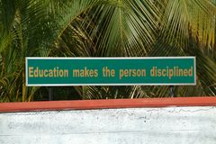 Motivational school sign. Saying education makes the person disciplined, tropical palm tree leaves in background Stock Photography