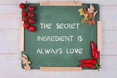 Motivationen uttrycker den hemliga ingrediensen är alltid förälskelse Lycka familj, hem som lagar mat begrepp Inspirerande citati Arkivbilder