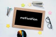 MOTIVATIONS-Wort auf Draufsicht der Tafel mit Gl?sern, Federkasten, Heftern und Markierung lizenzfreie stockfotografie
