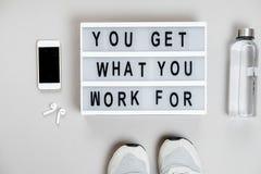 Motivazione di sport Vista superiore del telefono e delle scarpe da tennis su un backg grigio Fotografie Stock