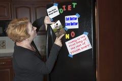 Motivazione stante a dieta di invio della donna sul frigorifero Fotografia Stock
