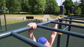 Motivazioni di sport di concetto Retrovisione di un uomo muscolare tirato su su una barra orizzontale all'aperto un giorno solegg archivi video