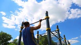 Motivazioni di sport di concetto Retrovisione di un uomo muscolare tirato su su una barra orizzontale all'aperto un giorno solegg stock footage