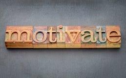 Motiveer woord in letterzetsel houten type blokken stock afbeelding