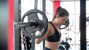 Motiverad idrottskvinna som squatting med den tunga skivstången på skuldror, aktiv genomkörare arkivfilmer