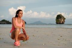 Motivierte sportliche Frau bevor dem Laufen am Strand stockfotografie