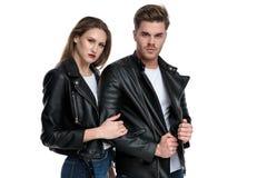 Motivierter junger Mann, der seine Jacke, umfassend von der Freundin zieht stockbild