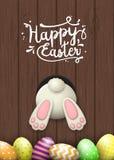 Motivo de Pascua, parte inferior del conejito y huevos de Pascua en el fondo de madera marrón, ejemplo ilustración del vector