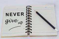 Motivwörter GEBEN NIE OBEN geschrieben auf eine Seite eines geöffneten Notizbuches mit Bleistift neben ihm Stockfotografie