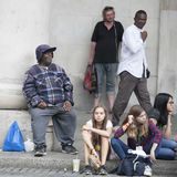 A motley crowd sitting on the pavement for rest Royalty Free Stock Images