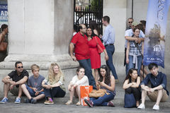 A motley crowd sitting on the pavement for rest Royalty Free Stock Photo