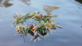 A motley grass wreath on the water. A motley grass wreath with candles on the water. Ethnic decor. Slavic tradition. Ivana Kupala pegan holiday stock video footage