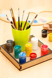 Motley paints and brushes in a cup ready for painting Stock Images