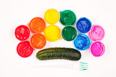Motley paints and cucumber isolated. Motley paints on the white background. paints arranged as rainbow with plastic fork partly colored in green paint and stock photo