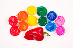 Motley paints and sweet pepper. Motley paints on the white background. paints arranged as rainbow with red sweet pepper (paprika). studio shot stock images