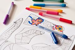 Motley pattern shoes and colour felt pens on table Stock Image