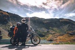 摩托车旅客年轻夫妇罗马尼亚的秋天山的 莫托旅游业和moto旅行家生活方式一会儿 免版税库存照片