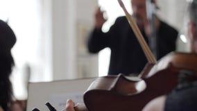 Moto accelerato, giochi del violinista su fiddle davanti ad un supporto musicale sul conduttore del fondo stock footage