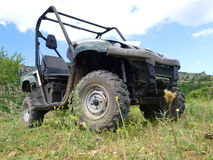 Moto all-terrain vehicle in mountains. Against blue sky Stock Image