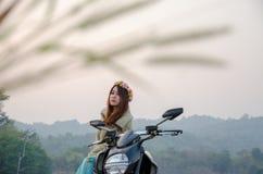 Moto asiática del montar a caballo de la mujer en campo tropical foto de archivo