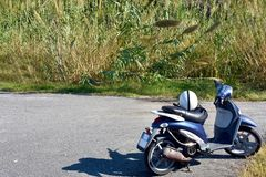 Moto azul parqueada delante de campo de lámina imagen de archivo