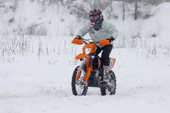 The moto bike's driver rides over snow track Royalty Free Stock Images