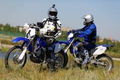 Moto biker driving enduro bike. Moto bikers driving enduro bike Royalty Free Stock Images