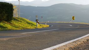Moto Biker Rides on a Mountain Road from the Turn. Landscape view of the Alps Mountains, Austria. Beautiful Mountain Road. Summer, day stock footage