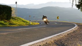 Moto Biker Rides on a Mountain Road from the Turn. Landscape view of the Alps Mountains, Austria. Beautiful Mountain Road. Summer, day stock video footage